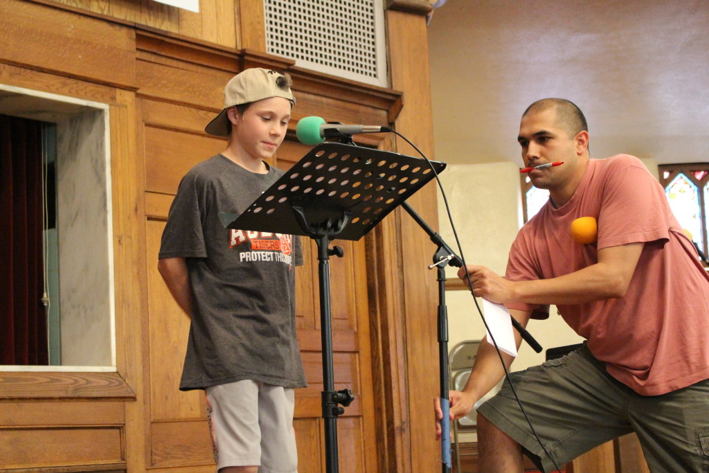 Robert Botello, right, adjusts the microphone for a student during the Freedom Academy's speech class. Photo by Benjamin McKnight III