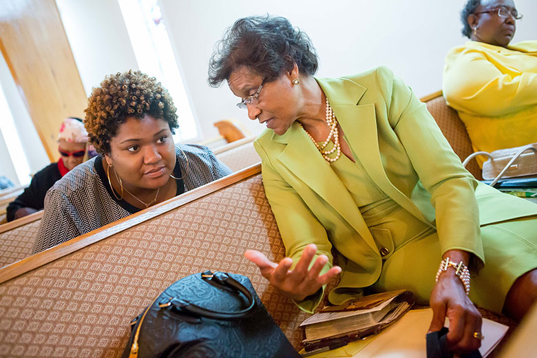 Morgan State student Camille Harrison, left, speaks with …. during services at Ebenezer Missionary Baptist Church while reporting for the Bridging Selma project in Selma, Alabama.